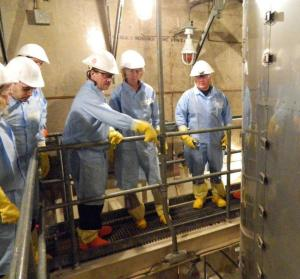 NRC Chairman Allison Macfarlane (second from right) listens as Southern California Edison executive Richard St. Onge (third from right) discusses issues with one of the damaged steam generators at SONGS. The steam generator is in the right foreground.