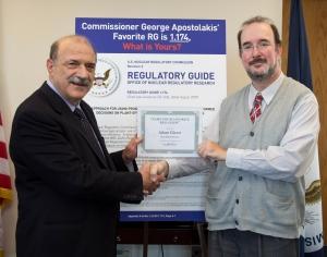 Commissioner Apostolakis congratulates contest winner Adam Glazer.