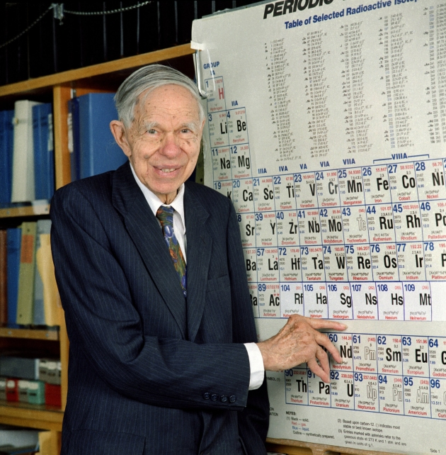 Chemist Glenn Seaborg stands next to a periodic table. He is pointing at the synthetic element seaborgium, which is named after him. Dr. Seaborg, a former Chairman of the Atomic Energy Commission, was awarded the Nobel Prize in Chemestry in 1951.