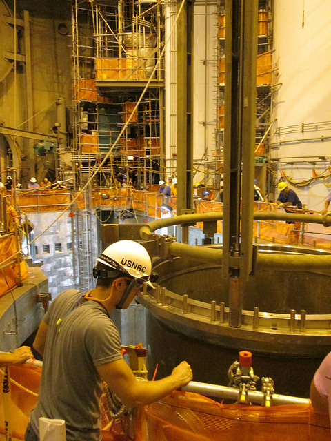 An NRC Construction Resident Inspector watches TVA staff install the reactor pressure vessel inside the containment building at Watts Bar Unit 2.