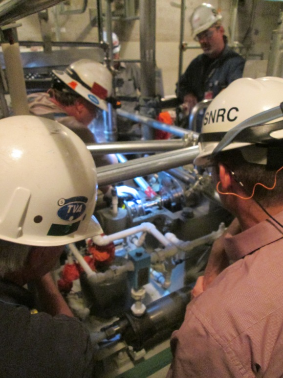 An NRC inspector looks on as TVA workers install components at Watts Bar Unit 2.